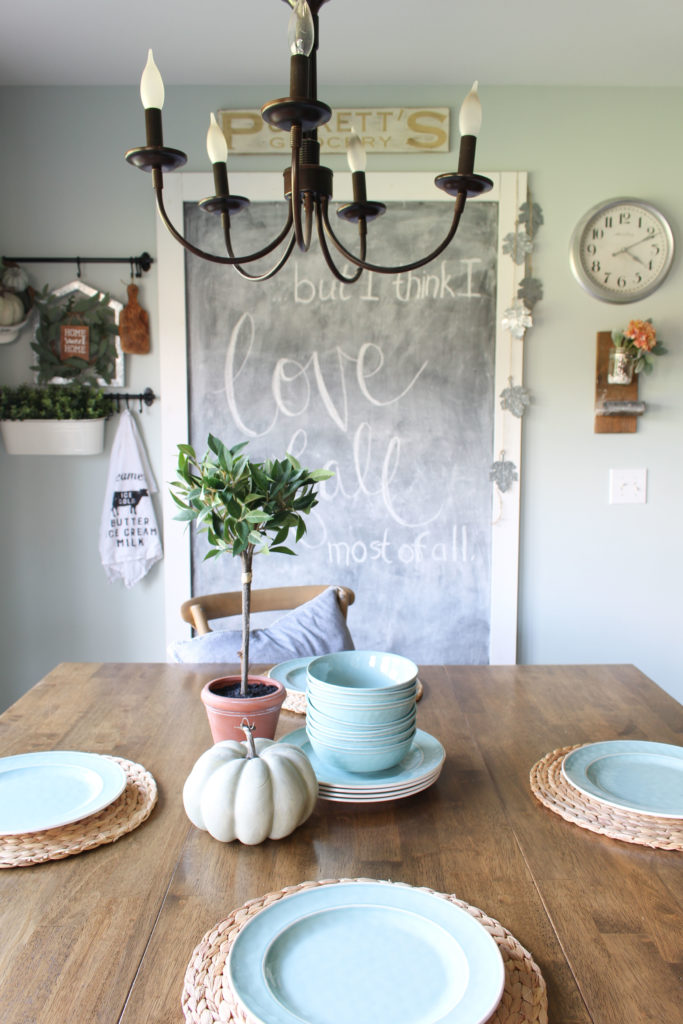 Eat-in kitchen area with a few simple fall touches, like a pumpkin on the table and a bay leaf topiary. #falldecor #homedecor #fallhometour