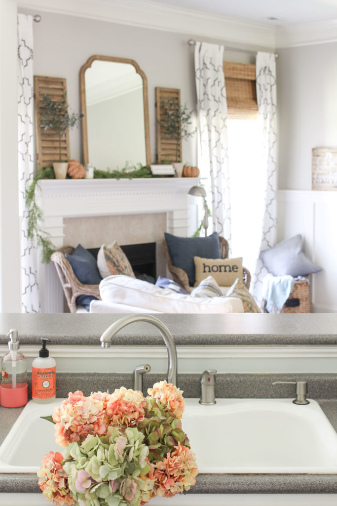 Green and coral pink hydrangeas grace the white sink in a cozy fall kitchen. Lots of fall home decor ideas in this post!